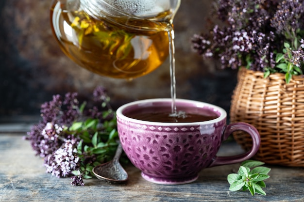 Healthy tea from oregano flowers in a beautiful mug on a wooden surface
