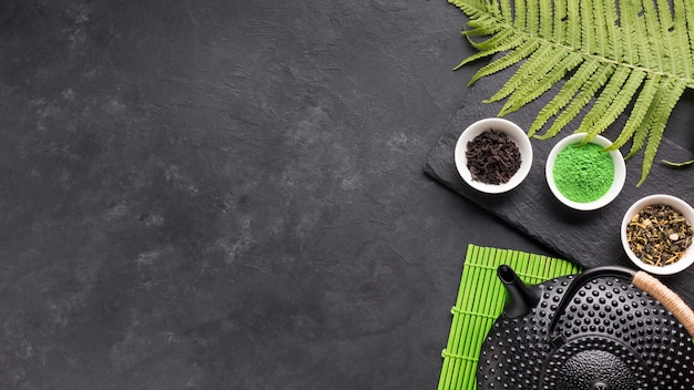 Healthy tea ingredient with black teapot and fern leaves over backdrop