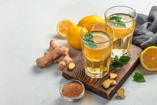 Здоровый чай с имбирем, лимоном и мятой на светлом фоне