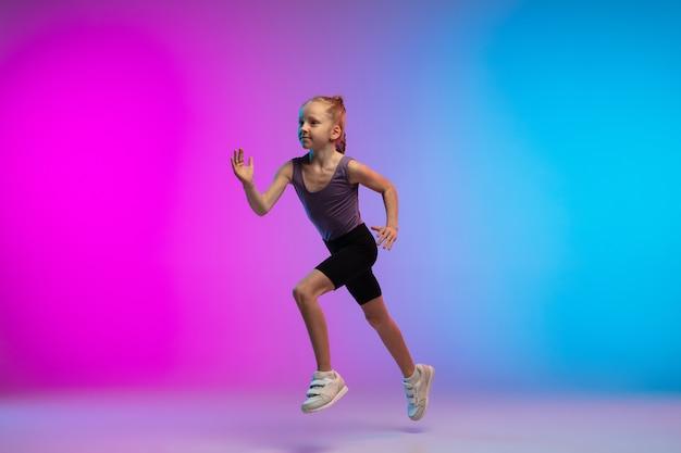 Salutare. ragazza adolescente, corridore professionista, pareggiatore in azione, movimento isolato su sfondo rosa-blu sfumato in luce al neon. concetto di sport, movimento, energia e stile di vita dinamico e sano.