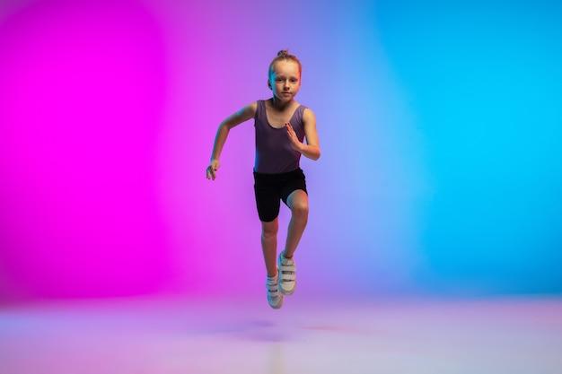 元気。 10代の少女、プロのランナー、ジョギングのアクション、ネオンの光の中でグラデーションピンクブルーの背景に分離された動き。スポーツ、運動、エネルギー、ダイナミックで健康的なライフスタイルのコンセプト。