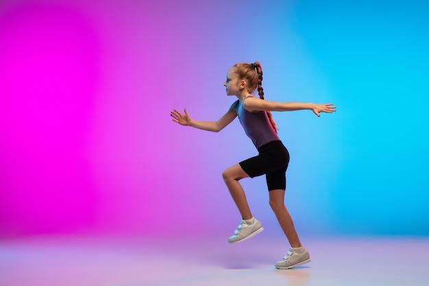 Здорово. девочка-подросток, профессиональный бегун, бегун в действии, движение, изолированное на градиентном розово-голубом фоне в неоновом свете. понятие спорта, движения, энергии и динамичного, здорового образа жизни.