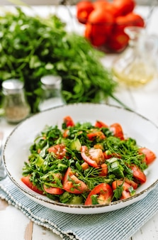 Healthy tomato salad with cucmbers, dill, onion and parsley