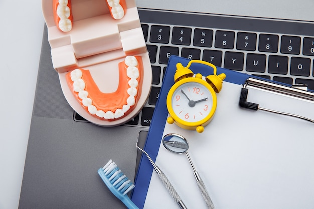 Модель здорового зуба с стоматологическим инструментом и будильником в кабинете стоматолога. концепция профессиональной гигиены зубов