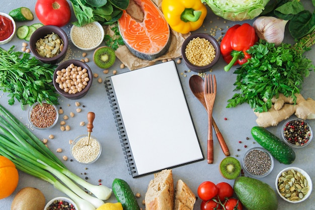 Healthy uncooked food frame background with copy space in blank notepad and keto diet and meal plan concept