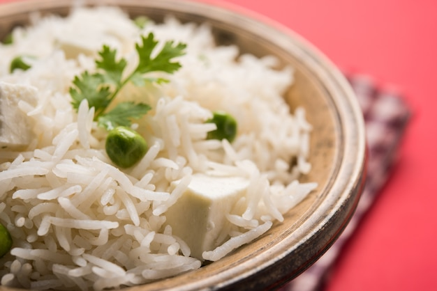 파니르, 완두콩, 바스마티 쌀을 사용한 건강한 채소 풀라프 또는 필라프. 변덕스러운 배경 위에 그릇에 제공됩니다. 선택적 초점