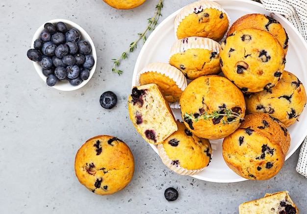 Healthy vegan banana blueberry muffins in a white ceramic bowl with berries, thyme and mint