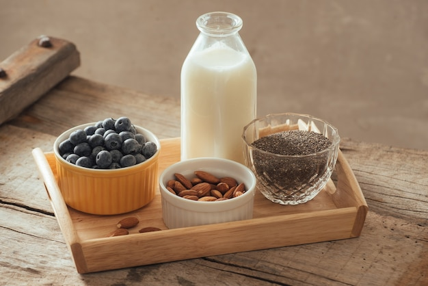 Здоровый веганский завтрак. молоко в бутылках с чиа, миндалем, свежими фруктами и ягодами на фоне деревянного стола, копией пространства. чистое питание, потеря веса, вегетарианство, концепция сырой пищи