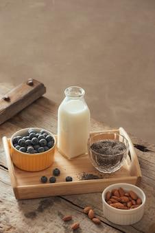 ヘルシーなビーガン朝食。木製のテーブルの背景、コピースペースにチア、アーモンド、新鮮なフルーツとベリーのボトル入り牛乳。きれいな食事、減量、菜食主義者、ローフードの概念