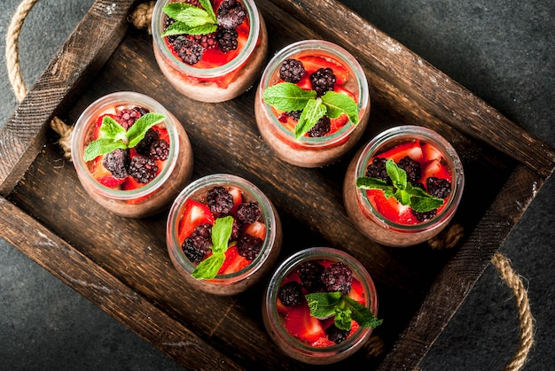 Healthy vegan breakfast. dessert. alternative food. pudding with chia seeds, fresh strawberries, blackberries and mint. on a dark stone background, in an old wooden tray. top view