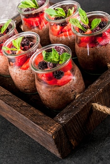 Healthy vegan breakfast. dessert. alternative food. pudding with chia seeds, fresh strawberries, blackberries and mint. on a dark stone , in an old wooden tray. close view