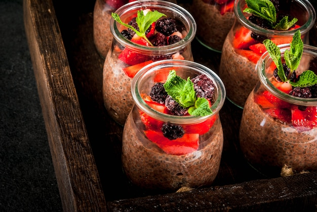 Healthy vegan breakfast. dessert. alternative food. pudding with chia seeds, fresh strawberries, blackberries and mint.  , in an old wooden tray. close view