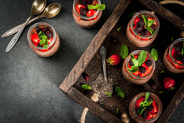 Healthy vegan breakfast. dessert. alternative food. pudding with chia seeds, fresh strawberries, blackberries and mint.  , in an old wooden tray.  top view