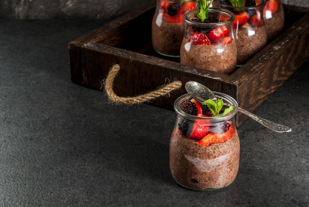 Healthy vegan breakfast. dessert. alternative food. pudding with chia seeds, fresh strawberries, blackberries and mint.  , in an old wooden tray.