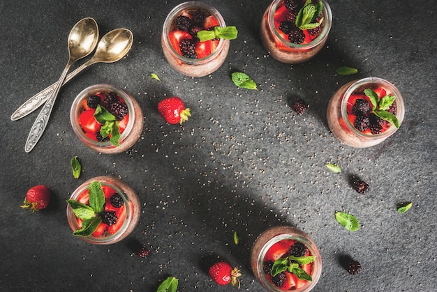 Healthy vegan breakfast. dessert. alternative food. pudding with chia seeds, fresh strawberries, blackberries and mint.   .  top view