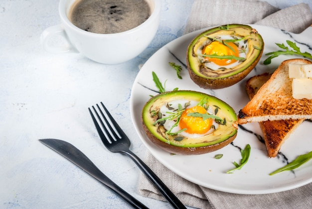 Healthy vegan breakfast. diet. baked avocado with egg and fresh salad from arugula, toast and butter. on a white marble plate, a light concrete table. a cup of coffee.