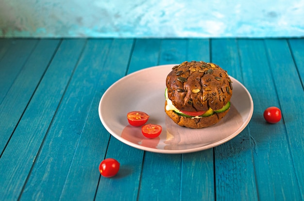 Healthy vegan burger with cheese, cucumber, tomato on plateon a bun with sunflower, sesame seeds and pumpkin seeds on light blue wooden table