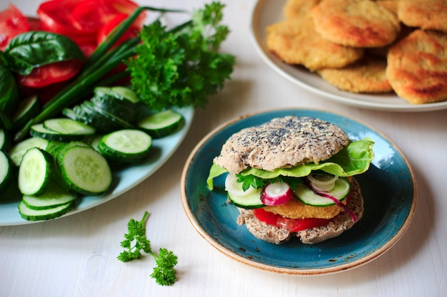Healthy vegan burger with chickpea fritters and wholewheat buns with sesame and poppy seeds