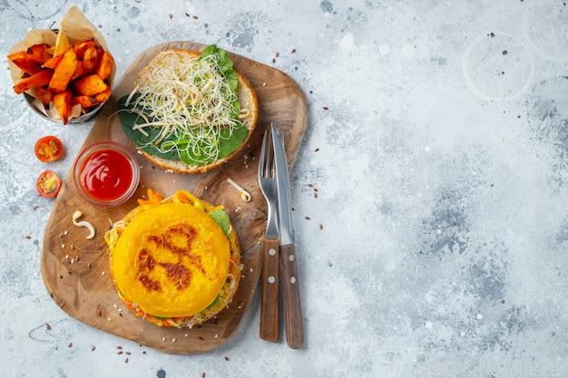 Здоровый веганский бургер со свежими овощами и белым соусом. вид сверху с копией пространства. плоская планировка.