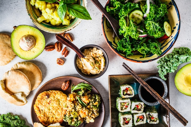 Healthy vegan food dinner. flat lay of stew with chickpeas, vegan bergrer, hummus, kale salad, vegan sushi rolls and tortillas.