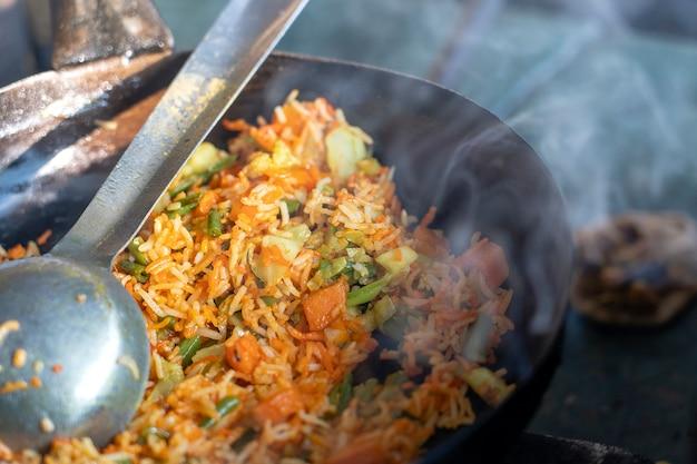 健康的なビーガンフード-インド料理の野菜ピラフまたはビリヤニ、クローズアップ。インドの地元の市場のストリートカフェで野菜のビリヤニを調理します。
