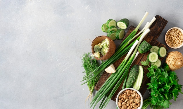 Healthy vegan food veggie cooking concept. wooden cutting kitchen board with fresh green vegetables, herbs and cereal on light background top view