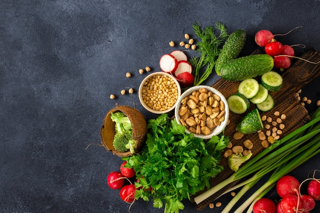 Healthy vegan food veggie cooking concept. wooden cutting kitchen board with fresh green vegetables, herbs and cereal top view