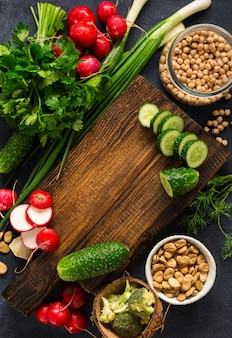 Healthy vegan food veggie cooking concept. wooden cutting kitchen board with fresh vegetables, herbs and cereal on dark background top view