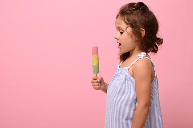 コピースペースの背景にピンクの壁を持つ4年のかなりゴージャスな女の赤ちゃんの手に健康的なビーガンアイスクリームアイスキャンディー。夏のデザートと陽気な夏の気分のコンセプト