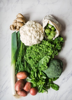 Healthy vegan ingredients for cooking. various clean vegetables and herbs on marble background. products from the market without plastic. flat lay