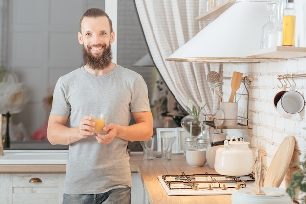 Healthy vegan lifestyle. balanced nutrition. man standing in kitchen with glass of orange juice, smiling. blur window wall.