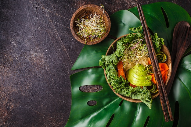 Healthy vegan lunch in coconut bowl. buddha bowl on a dark background.