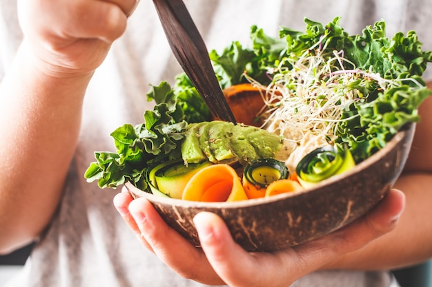 Healthy vegan lunch in a coconut bowl. a child eating buddha bowl.