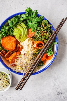 Healthy vegan lunch in white bowl. buddha bowl with avocados