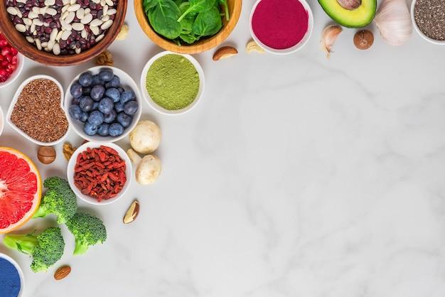 ホワイトマーブルテーブルでのヘルシーなビーガンまたはベジタリアン料理。野菜、果物、ナッツ、スーパーフード。フラットレイ。コピースペースのある上面図