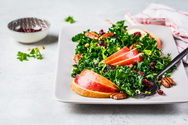 Healthy vegan salad with apple, cranberry, kale and pecan in a rectangular plate.