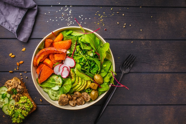 Healthy vegan salad with baked vegetables and avocado in white bowl with avocado toast on dark wooden background.