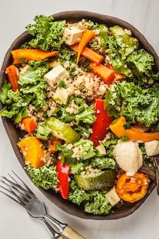 ロースト野菜、タヒニ、キノア、ケールのヘルシービーガンサラダ。きれいな食事のコンセプトです。