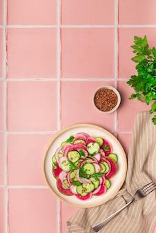 Здоровый веганский салат с арбузом, редисом, огурцом и красным луком на фоне розовой плитки