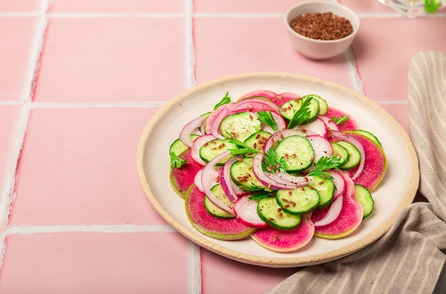 Здоровый веганский салат с арбузным редисом, огурцом и красным луком на фоне розовой плитки.