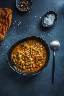 Healthy vegan stew ragout with tofu served in bowl on dark background. closeup