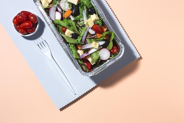 Здоровый веганский салат на вынос в алюминиевом контейнере или доставка еды