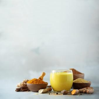 Healthy vegan turmeric latte or golden milk, turmeric root, ginger powder, black pepper over grey concrete background.