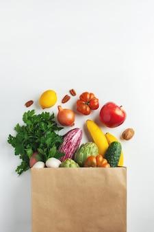 Здоровая веганская вегетарианская еда в бумажном пакете с овощами и фруктами на белом