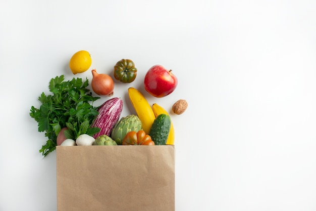 Healthy vegan vegetarian food in paper bag vegetables and fruits on white, copy space. shopping food supermarket and clean vegan eating concept.