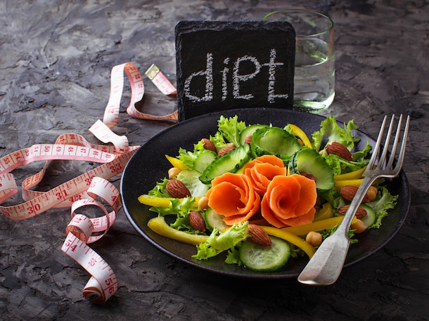 Healthy vegetable salad, glass of water and  tape measure. diet concept. selective focus