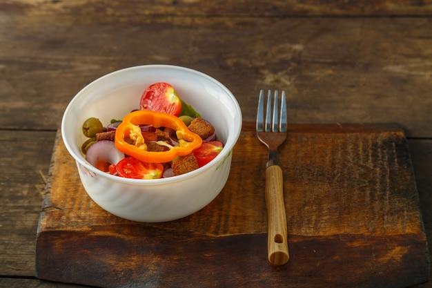 포크 옆에 있는 나무 테이블에 있는 샐러드 그릇에 건강한 야채 샐러드. 가로 사진