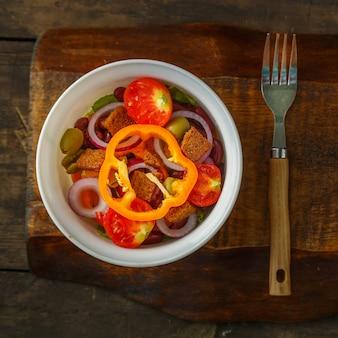 포크 옆에 있는 나무 테이블에 있는 샐러드 그릇에 건강한 야채 샐러드.