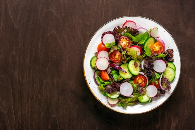 チェリートマト、きゅうりのスライス、緑と紫のレタスの葉、玉ねぎ、オリーブオイルのヘルシーな野菜サラダを木製のテーブルに載せた上面図フラットレイダイエット、地中海料理ビーガン料理。