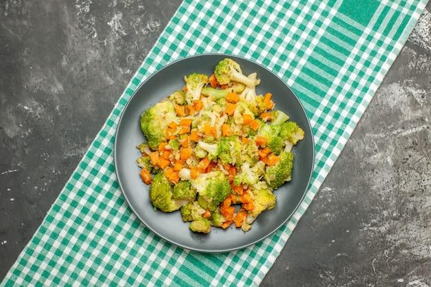 灰色のテーブルの上の緑のストリップタオルの上の健康的な野菜サラダ